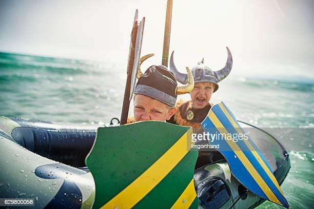 Kids playing vikings at sea on a boat