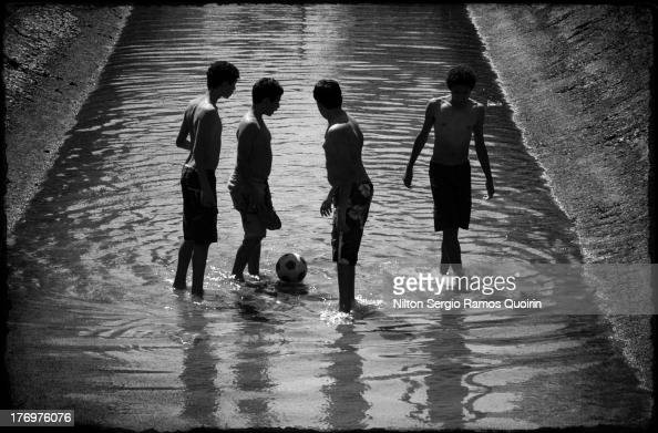 CONTENT] Kids playing with a soccer ball in a canal in Santos