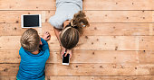 Top view image of two kids lying on the floor and playing with tablet and smartphone watching movie or gaming. Mockup or template for web or application design.