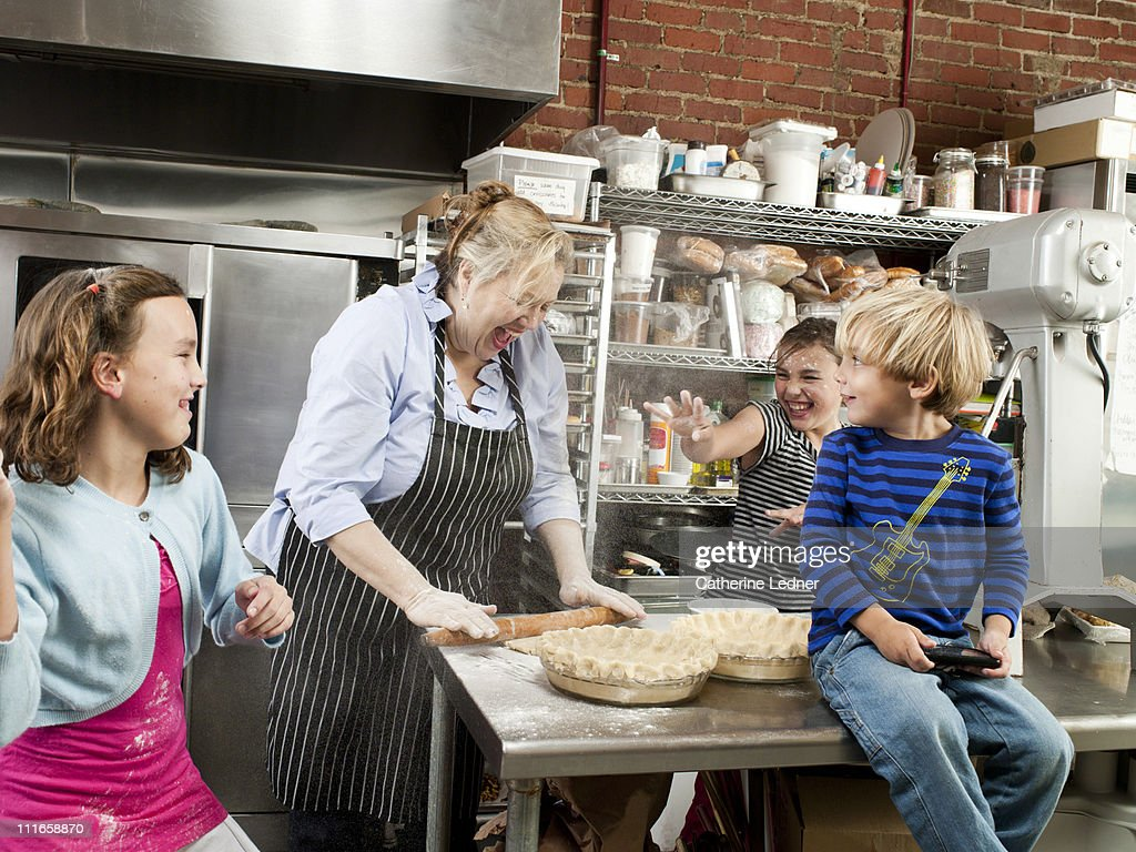Kids playing with mother in family-owned bakery : Stock Photo