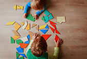 little boy and girl playing with puzzle, education concept