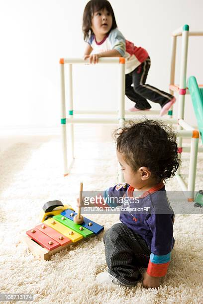 Kids playing with xylophone and jungle gym