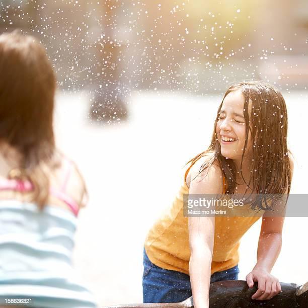 Kinder spielt mit dem Wasser
