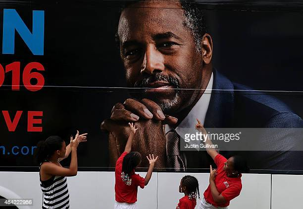 Kids pose for a photo in front of the campaign bus of republican presidential hopeful Ben Carson after church services at Maple Street Missionary...
