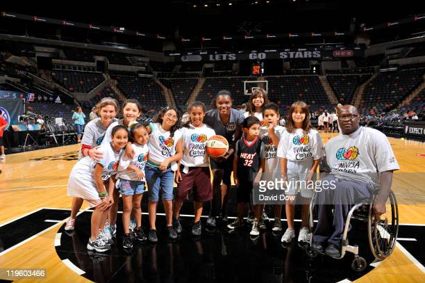 Kids poses with Marie FerdinandHarris of the Phoenix Mercury for a photo during the Jamba juice WNBA Fit Clinic as part of the 2011 WNBA Cares...