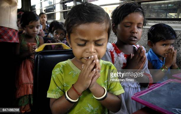 Kids praying before lunch inside a bus which is converted in to a school by Vision Rescue a social organisation for street children in Dadar Mumbai...