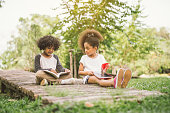 little Afro child girl reading book between green spikes meadow garden with friend  read education concept