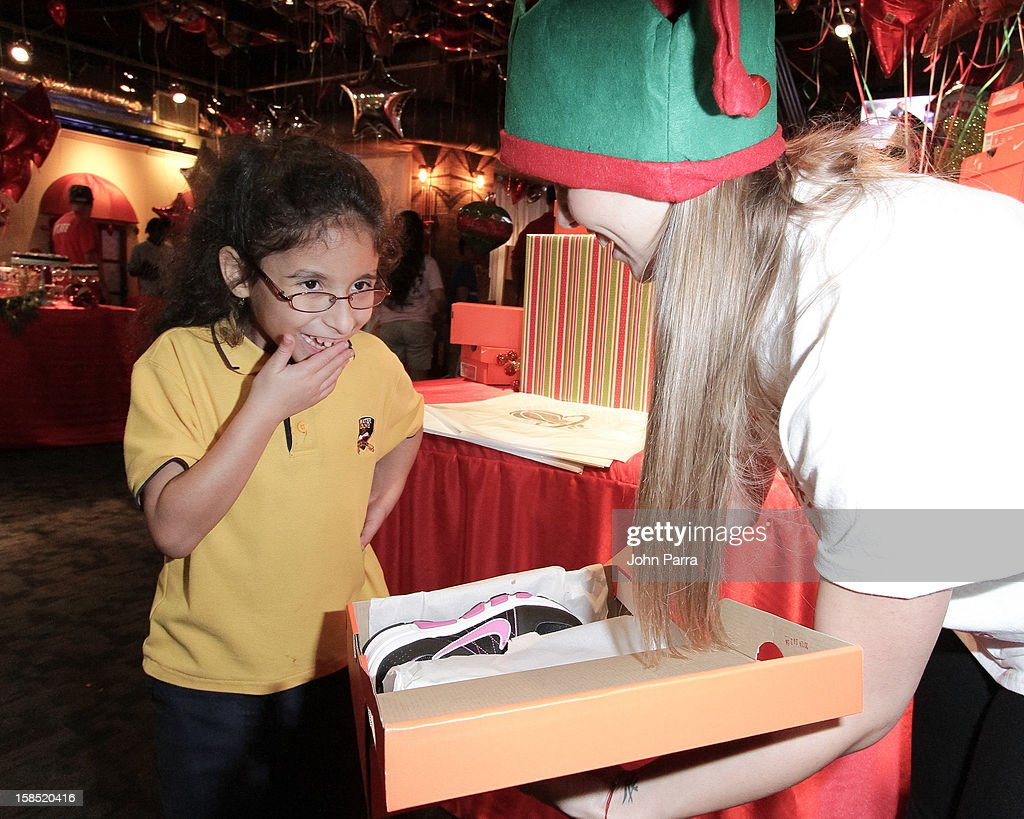 Kids receiving gifts during the Christmas With Chris Bosh At 'Santa Bosh's Workshop at Game Time at Sunset Place on December 17, 2012 in Miami, Florida.