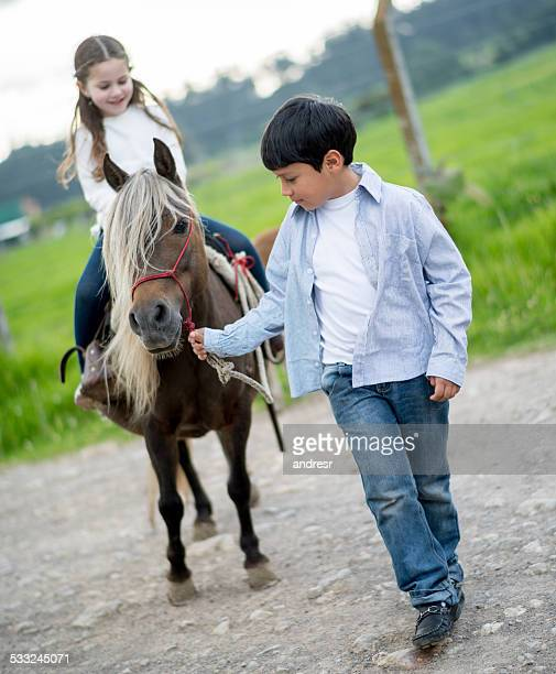 Kids riding a pony