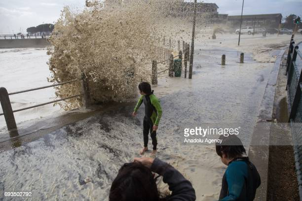 Kids run over the bridge as the huge waves hit coastline during the heavy storm in Cape Town South Africa on June 7 2017