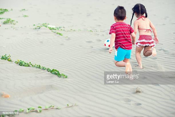 Kids running after football on beach