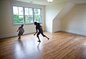 Crianças a correr à volta sala vazia em Nova casa