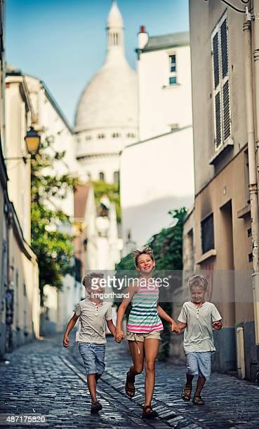 Kids running in beautiful street of Paris montmartre