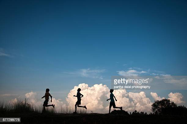 Kids running in clouds silhouette