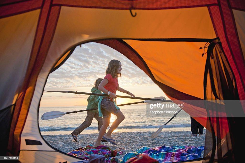 kids running on the beach with kayak paddles : Stock Photo