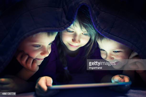 Kids secretly reading book on digital tablet