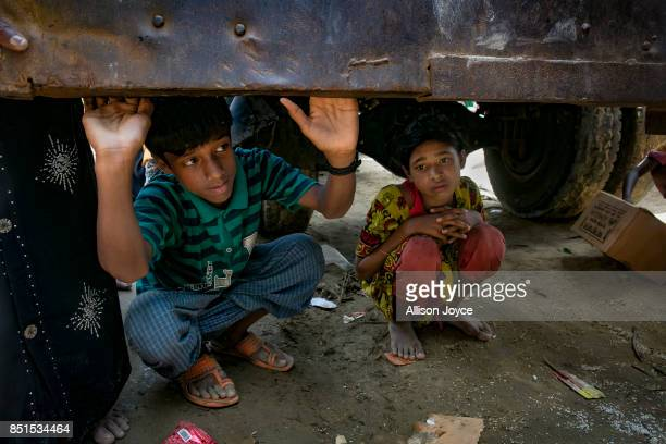 COX'S BAZAR BANGLADESH SEPTEMBER 22 Kids shelter under a truck during an aid distribution on September 22 2017 in Cox's Bazar Bangladesh Over 230000...