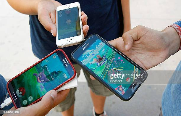 Kids show the screen of their smartphone with Nintendo Co's Pokemon Go augmentedreality game at the Trocadero in front of the Eiffel tower on...