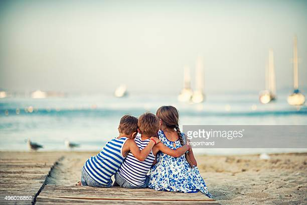 Kids sitting at the beach at the evening and embracing