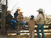 Siblings and father sitting on fence of corral in Big Timber, Montana