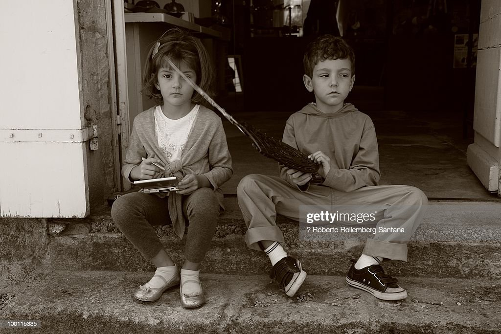 Kids sitting serious playing : Stock Photo