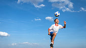 happy boy playing football on sky background