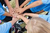 Kids soccer team huddled together during game; hands in circle
