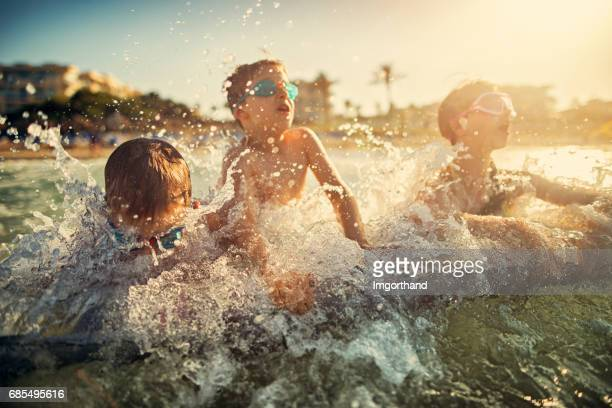 Kids splashed by sea wave