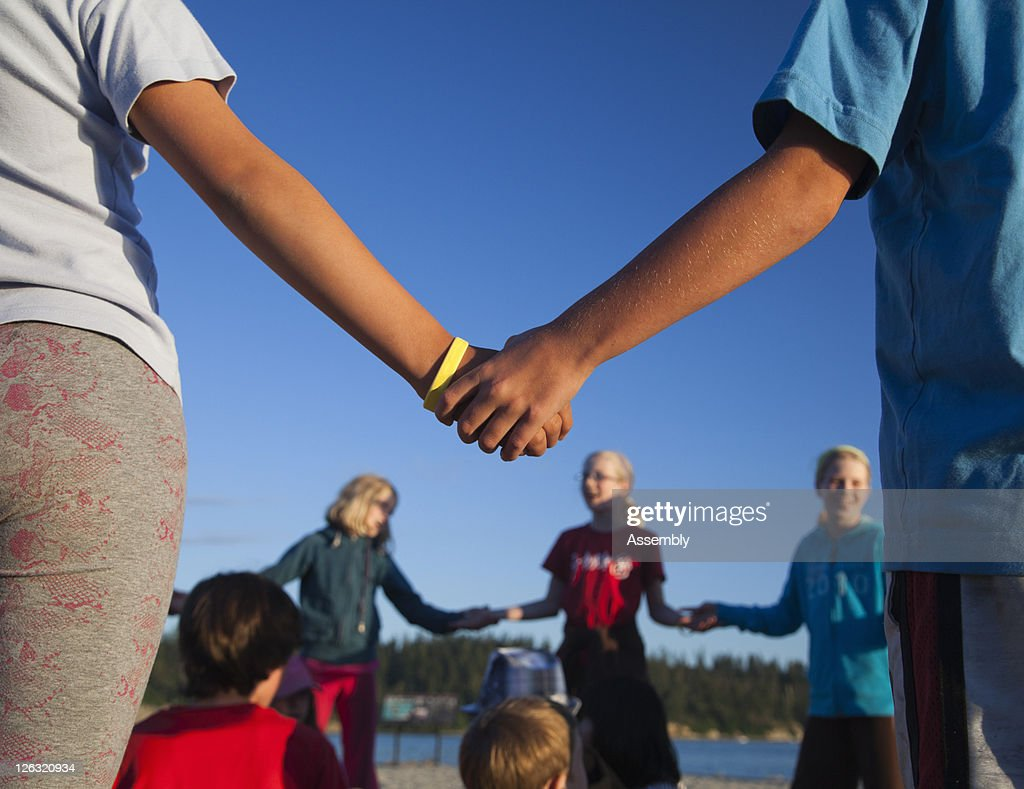 Kids standing in a circle holding hands : Stock Photo