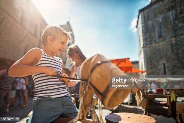 Kinderen toeristen plezier op carrousel in Volterra, Toscane