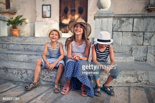 Kids tourists resting on stairs in beautiful majorcan city of Alcudia : Stock Photo