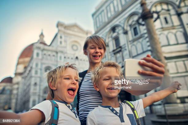 Kids tourists taking selfie in Florence, near the cathedral