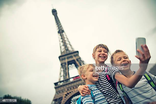 Kids tourists taking selfie near Eiffel Tower