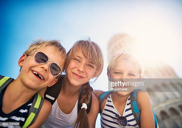Kids tourists taking selfies by the Leaning Tower of Pisa