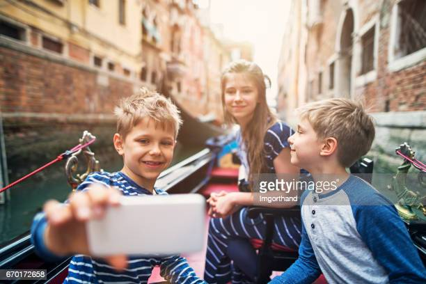 Kids tourists talking selfie during gondola ride in Venice, Italy