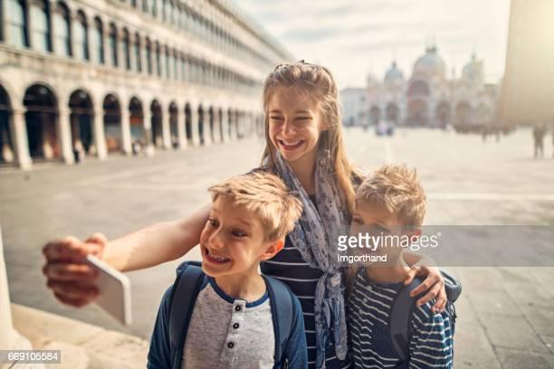 Kids tourists talking selfie in Piazza San Marco in Venice