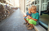 Kids tourists using smartphone in a street of Pisa, Italy
