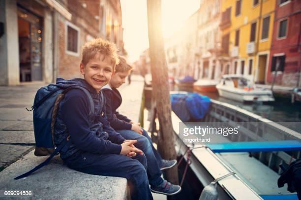 Kids tourists walking in street of italian town in Tuscany