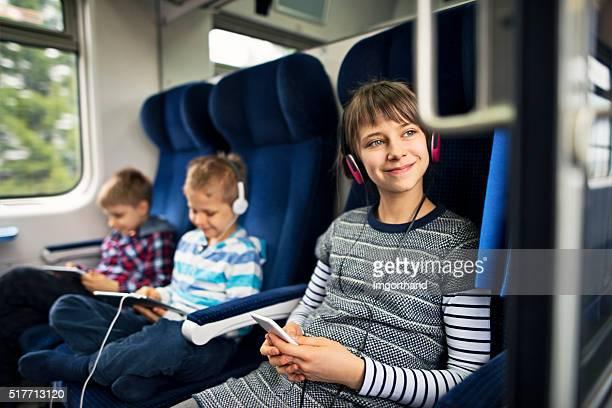 Kinder, die auf Zug spielen Tablet und Musik hören