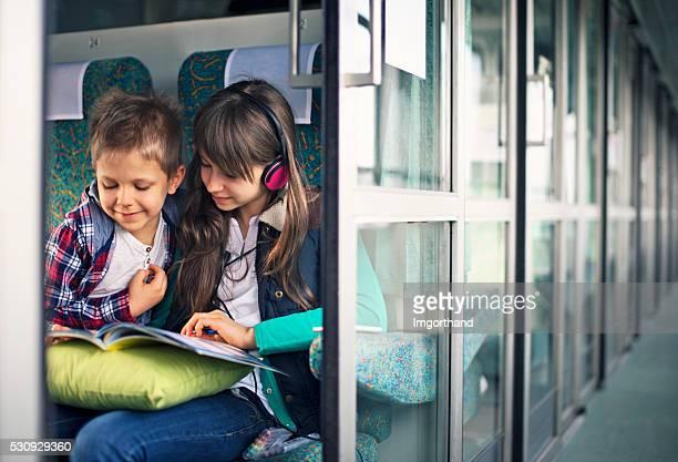 Kinder reisen mit dem Zug lesen Buch und beim Musikhören