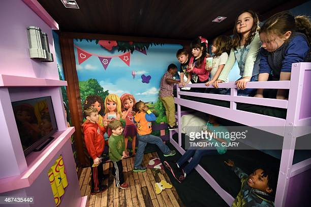 Kids try out a fullsized replica of its new room theme during a media event in New York March 24 2015 to promote the LEGOLAND® Hotel to open May 15...
