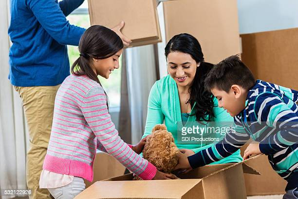 Kids unpack teddy bear from box