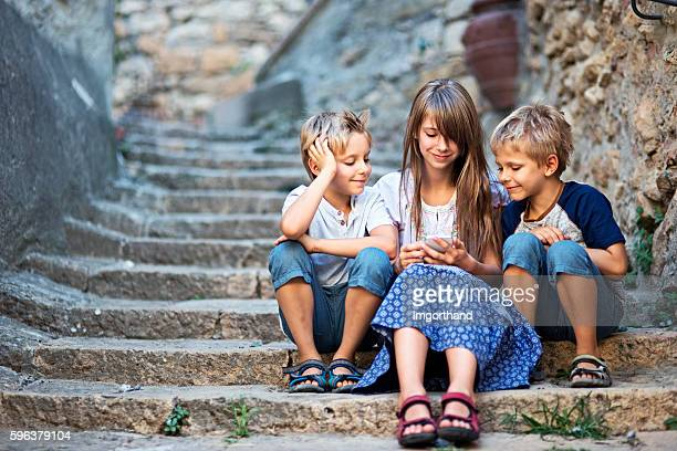 Kids using smartphone on an old weathered stairs