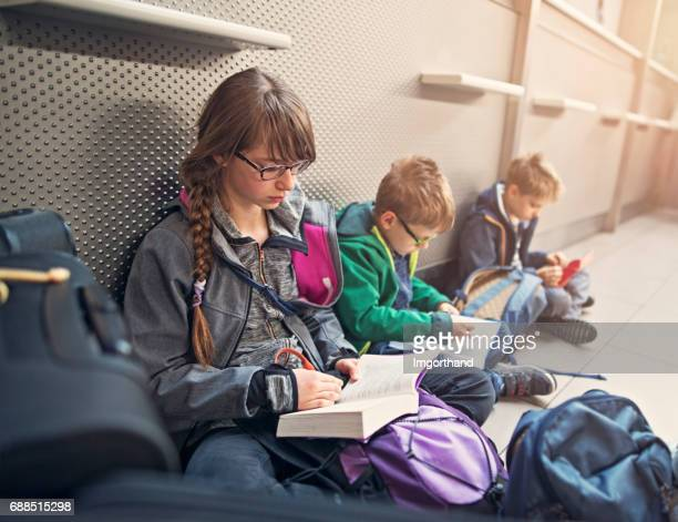 Kids waiting at the airport and reading books