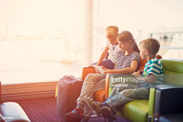 Kids waiting at the Paris airport playing with tablet