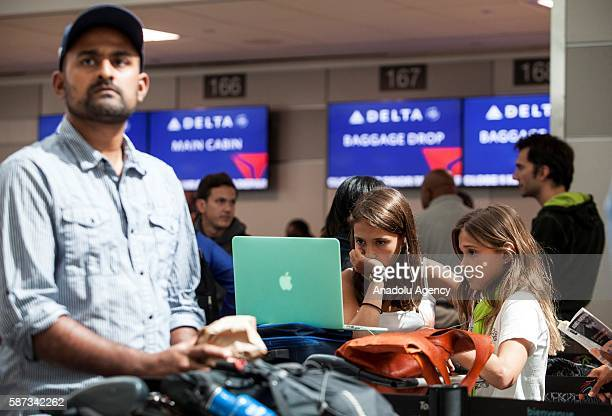 Kids watch a laptop screen as they wait for information from Delta airline employees at Pearson International airport in Toronto Canada on August 8...