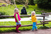 Two little kids, boy and girl, watch monkey show in the zoo on a cold autumn day. Children watching animals in safari park.