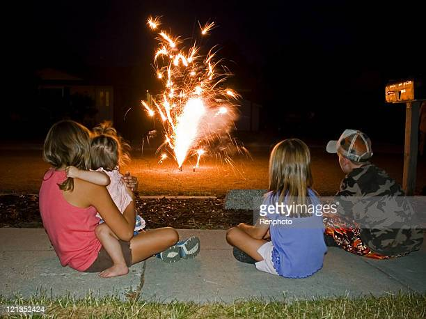 Enfants en regardant des feux d'artifice à la maison