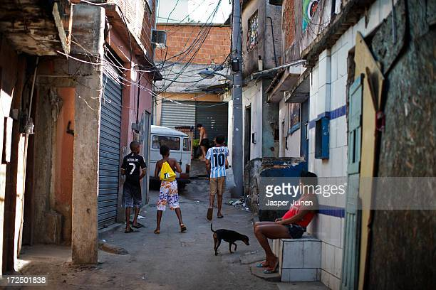 Kids wearing Lionel Messi and Cristiano Ronaldo football shirts walk through an alley of the Complexo do Alemao favela on June 29 2013 in Rio de...