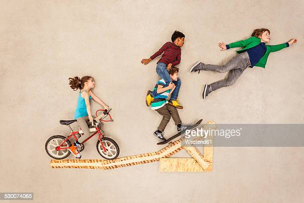 Kids with bike and skateboard on jump